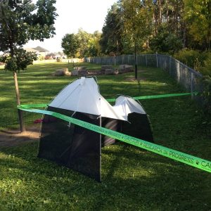 A Malaise Trap, a tent-like apparatus used to collect flying insects, is set up in a school yard during the spring.